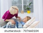 mother measuring temperature of ... | Shutterstock . vector #707660104