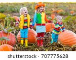 Small photo of Little girl, boy and baby picking pumpkins on Halloween pumpkin patch. Children playing in field of squash. Kids pick vegetables on a farm in Thanksgiving holiday season. Family having fun in autumn