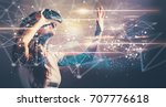 Stock photo links with young woman using a virtual reality headset 707776618
