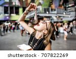 Stock photo young woman eating herring with onions traditional dutch snack in rotterdam market 707822269