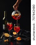 Small photo of Sangria poured into glasses from a jug. Traditional Spanish drink based on red wine and citrus fruit. Female hands. Black background. Copy space