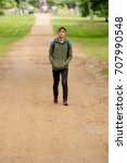Teenage boy walking in a park on a summers afternoon - stock photo
