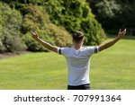 Teenage boy with his arms outstreched on a summer's day - stock photo