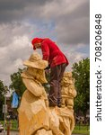 Small photo of SUZDAL, RUSSIA - JUNE 29, 2017: Chainsaw artist climbed onto his sculpture with chainsaw in his hands. Logger sport festival. Documentary editorial