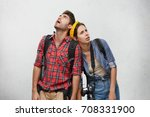 Small photo of Studio shot of young man and woman travelers in sensible clothes carrying heavy backpacks leaning on each other, feeling exhausted and thirsty while hiking. Travel, peolple and relationships concept
