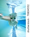 little boy swimming freestyle, seen from underwater - stock photo
