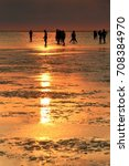 Small photo of Citizen and travelers enjoy sunset moment by walking in the intertidal zone under purple sunset background by filter in Gaomei Wetland, Taichung, Central Taiwan, Taiwan