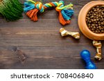 Stock photo bowl full and overflowing with dry pet dog food bits and toys on wooden background top view mock 708406840