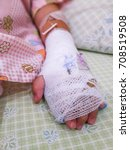 Small photo of Asian kid patient, Close up of iv plug in patient's child hand.heparin lock in hospital with saline intravenous (IV) drip