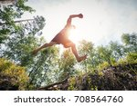 young man jumping in the forest.... | Shutterstock . vector #708564760