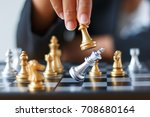 Small photo of Close up shot hand of business woman moving golden chess to defeat and kill silver king chess on white and black chess board for business challenge competition winner and loser concept, selective