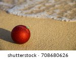 Red Christmas Ball On The Sand...