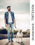 Stock photo handsome young man with labrador outdoors man on a walk in the city with his dog 708732436