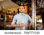 handsome young bartender holds... | Shutterstock . vector #708777130
