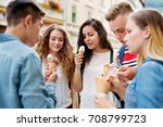 Small photo of Attractive teenage students in town eating ice cream.
