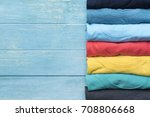Small photo of close up of rolled colorful clothes on wood table background