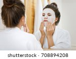 woman is applying sheet mask on ... | Shutterstock . vector #708894208