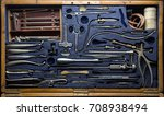 Small photo of Aged nurse physician accessory in container on blue backdrop. Aseptic hemostat, hypodermic tube, hospital extraction forcipes, steel hand lancet, tooth probe clamp device. Close up obsolete object