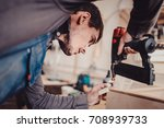 man builds furniture in the... | Shutterstock . vector #708939733