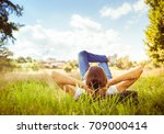 young woman lying on grass... | Shutterstock . vector #709000414