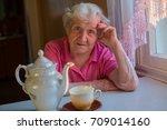 an elderly woman sitting at a... | Shutterstock . vector #709014160