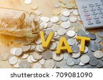 Small photo of Vat Concept.Word vat put on coins and calculator on table.