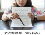 Small photo of Hand of woman broker shown to client where to sign signature contract.