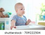 cute baby sitting in kitchen | Shutterstock . vector #709222504