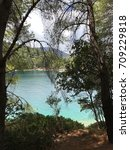 Small photo of Turquoise sea between a forest of pines in a bay in Ithaka or Ithaca, Greece.