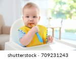cute baby with spoon sitting in ... | Shutterstock . vector #709231243