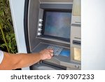 young woman withdrawing money  | Shutterstock . vector #709307233