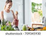 smiling woman squeezing orange... | Shutterstock . vector #709345930