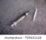 syringe and needle on concrete... | Shutterstock . vector #709631128