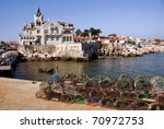 Fishing traps and anchored fishing boat in a port of Cascais, Portugal. - stock photo