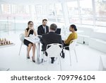 Small photo of Cheerful colleagues celebrating accomplished startup communicating on meeting table in modern interior office.Prosperous business partners satisfied with successful parley results on meeting