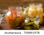 Small photo of Fermented preserved vegetables on a dark background.