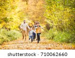 Stock photo beautiful young family on a walk in autumn forest 710062660