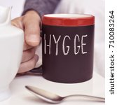 Small photo of closeup of a young man with a mug with coffee or tea, where there is the text hygge, a danish and norwegian word for comfort or enjoy, which can be a whole philosophy of life