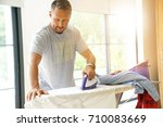 man at home ironing clothes | Shutterstock . vector #710083669