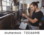 young waiter washing plates... | Shutterstock . vector #710166448