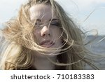 Small photo of A young girl a black short mini dress with strasses posing on the pantone (landing stage) of the Volga River. Russia.