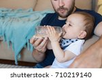 young father feeding his baby... | Shutterstock . vector #710219140