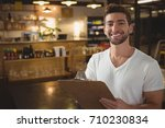 portrait of smiling waiter with ... | Shutterstock . vector #710230834