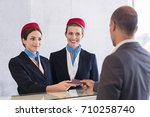 Small photo of Woman in checkin counter taking passport for verification from passenger man. Happy smiling hostess at check in working with her colleague. Businessman on a business trip in airport.