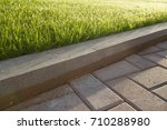 Small photo of road and lawn divided by a concrete curb
