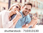couple eating sandwiches on a... | Shutterstock . vector #710313130