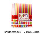 Small photo of A colorful package with red, yellow and pink stripes and a signification happy birthday isolated on a white background.