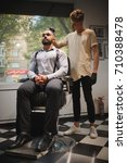 Small photo of Barber with a hairbrush working on a new haircut for a client. Bearded client at the barbershop background. Copy space.