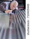 Small photo of senior man doing quality control in aluminium factory