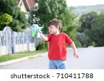 little boy playing with soap... | Shutterstock . vector #710411788